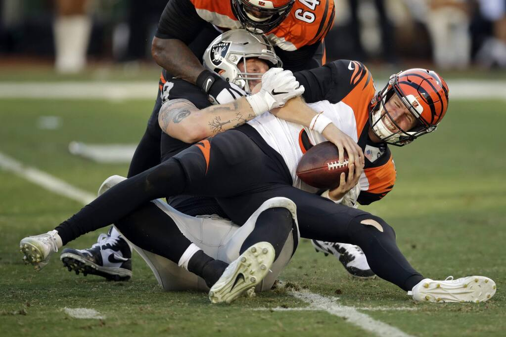 Cincinnati Bengals quarterback Ryan Finley, front, is sacked by Oakland Raiders defensive end Maxx Crosby during the second half in Oakland, Sunday, Nov. 17, 2019. (AP Photo/Ben Margot)