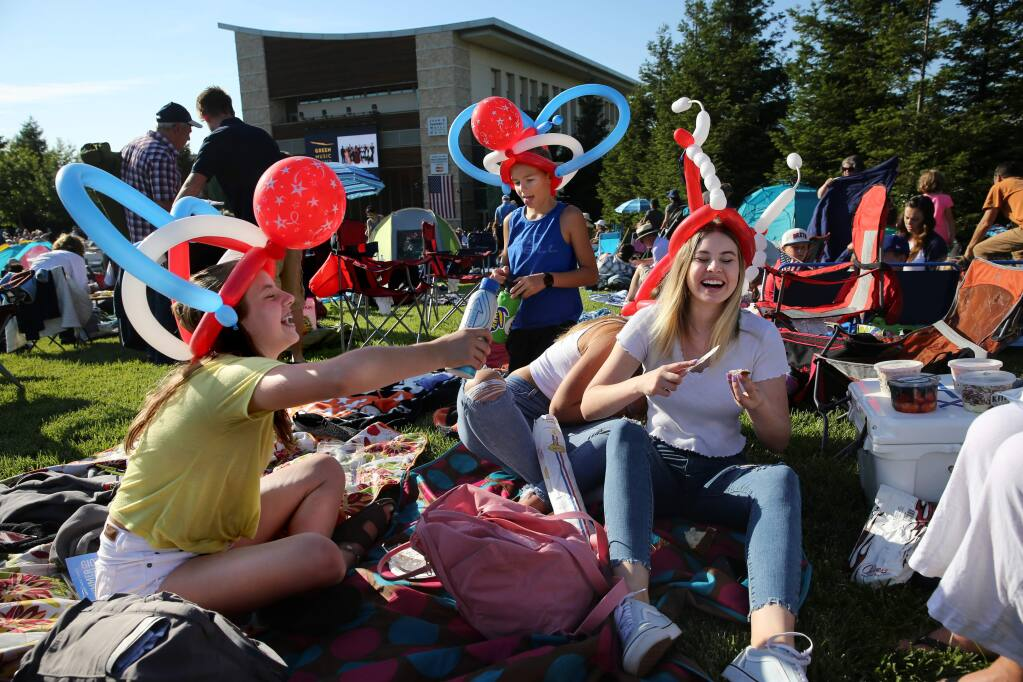 Abby Smits, 13, left, friend Jeremiah Kellison, 12, rear, and her sister Emma Smits, 16, right, attend the 4th of July Fireworks Spectacular event at the Green Music Center at Sonoma State University in Rohnert Park, California on Thursday, July 4, 2019. (BETH SCHLANKER/The Press Democrat)