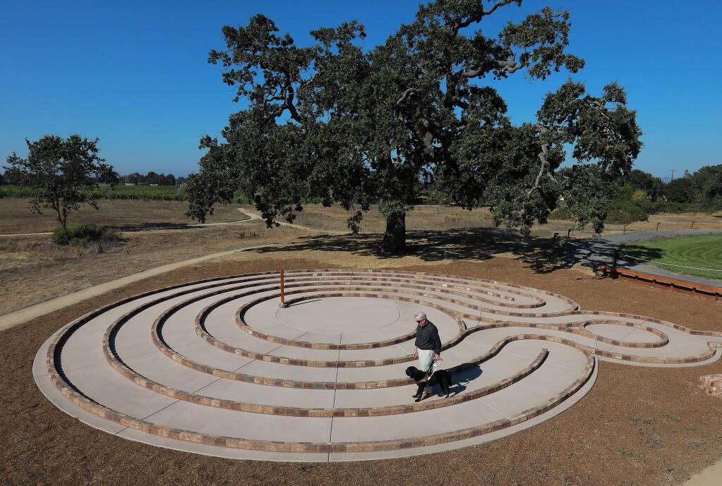 Bob Sonnenberg, who is legally blind, walks around the new labyrinth with his dog Langley at the Earle Baum Center for the Blind in Santa Rosa. (John Burgess/The Press Democrat)