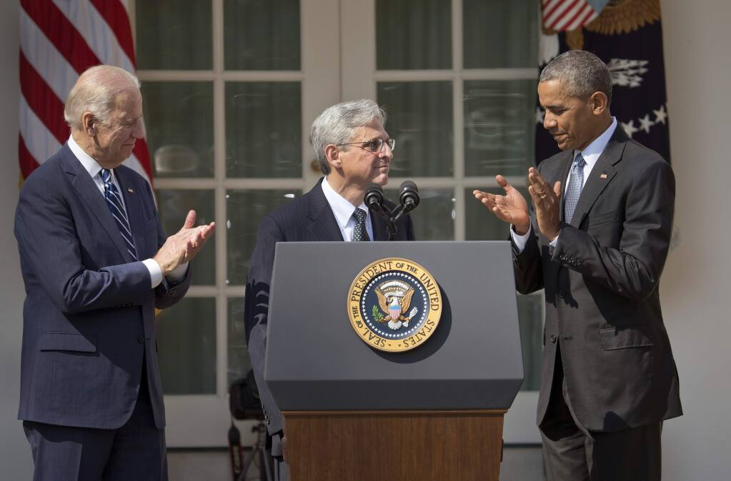 Supreme Court nominee Merrick Garland stands with President Barack Obama and Vice President Joe Biden in the White House rose garden on Wednesday. (PABLO MARTINEZ MONSIVAIS / Associated Press)
