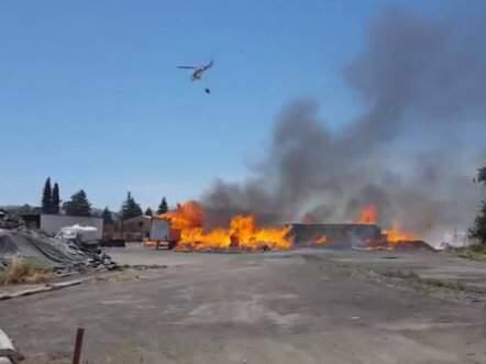 A helicopter helps fight the fire raging at a Schellville wooden pallet factory on Tuesday, June 5, 2018. (FACEBOOK LIVE/ SONOMA INDEX-TRIBUNE)