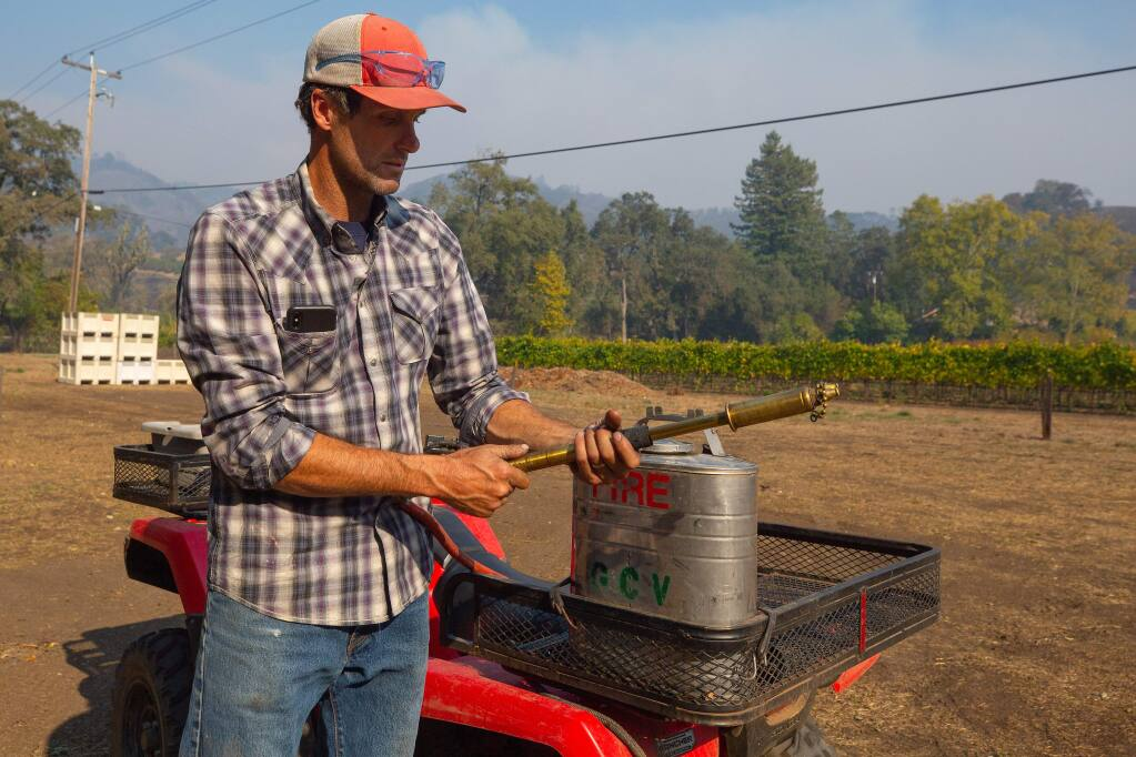Justin Miller of Garden Creek Vineyards shows one of the back pumps he and his vineyard workers used to protect his winery when the Kincade Fire erupted, in Geyserville, California, on Friday, October 25, 2019. (Alvin Jornada / The Press Democrat)