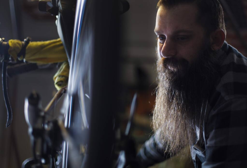 Petaluma, CA, USA. Tuesday, December 13, 2016._ Tim Nicholls, a bike repairman at Bruce Gordon Cycles, has been repairing bikes that he will donate to COTS. His program called 'Mending the Wheel' hopes to give the shelter 40 or 50 bikes for Christmas. (CRISSY PASCUAL/ARGUS-COURIER STAFF)