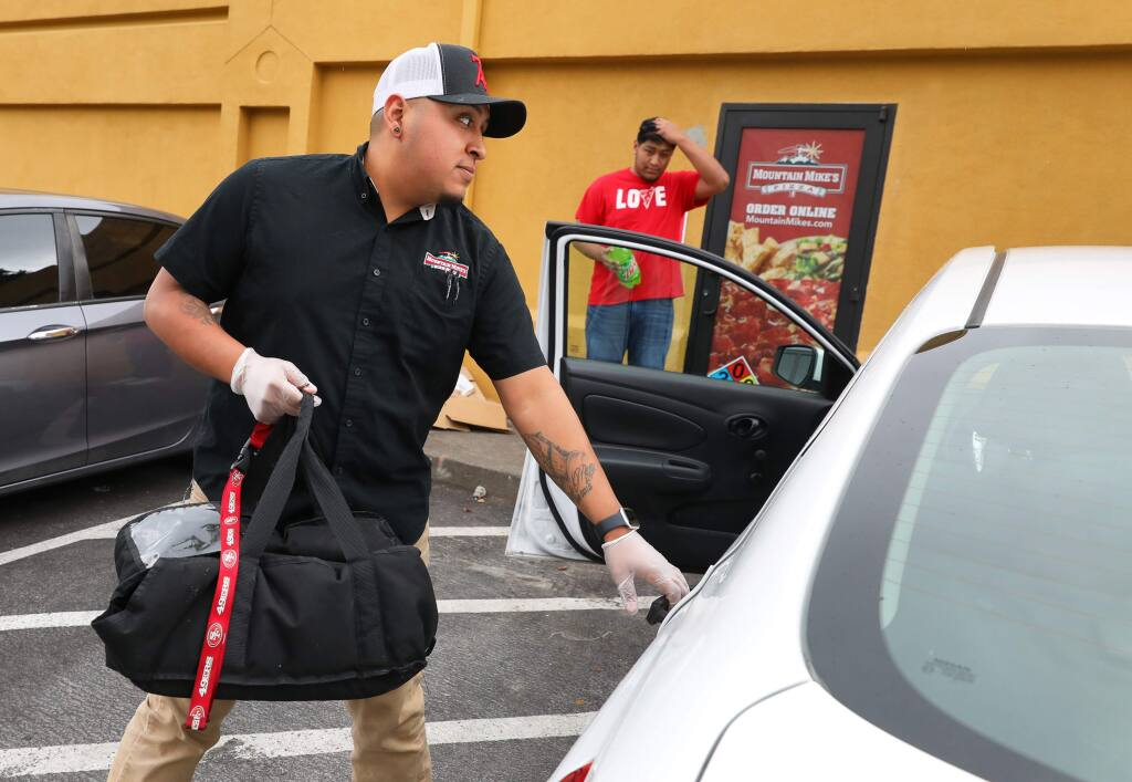 Alfredo Meza prepares to make a delivery for Mountain Mike's Pizza in Santa Rosa on Monday, April 6, 2020. The owner of the pizza chain secured a Small Business Administration loan during the first round of funding.(Christopher Chung/ The Press Democrat)