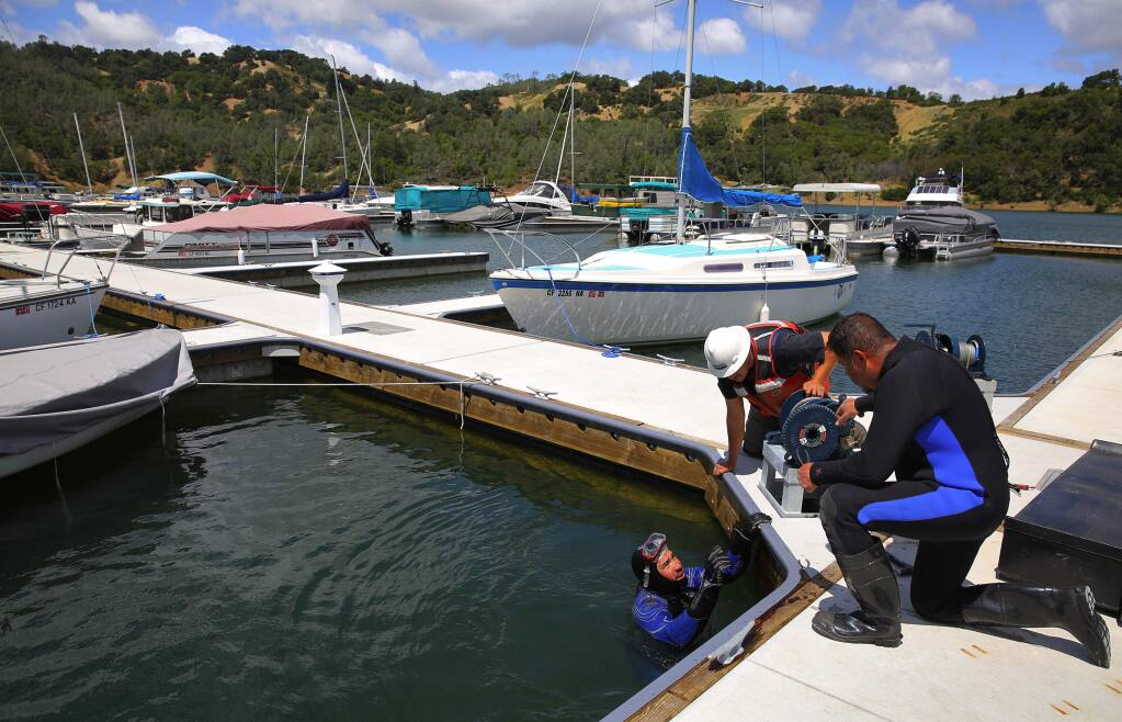 Odon Peralta, left, Filiberto Barron and Luis Vega work on putting the completing the new dock and boat slips at Lake Sonoma, on Friday, May 20, 2016. (Christopher Chung/ The Press Democrat)