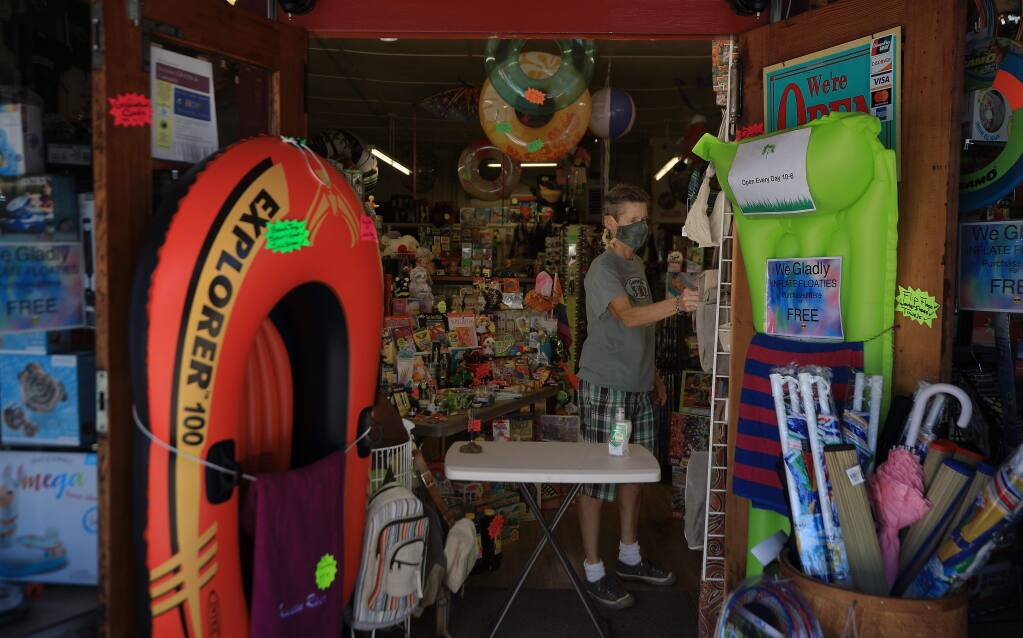 Guerneville 5 and 10's Robin Johnson straightens display items, Thursday, May 21, 2020 as Guerneville's business district gears up for Memorial Day. (Kent Porter / The Press Democrat) 2020