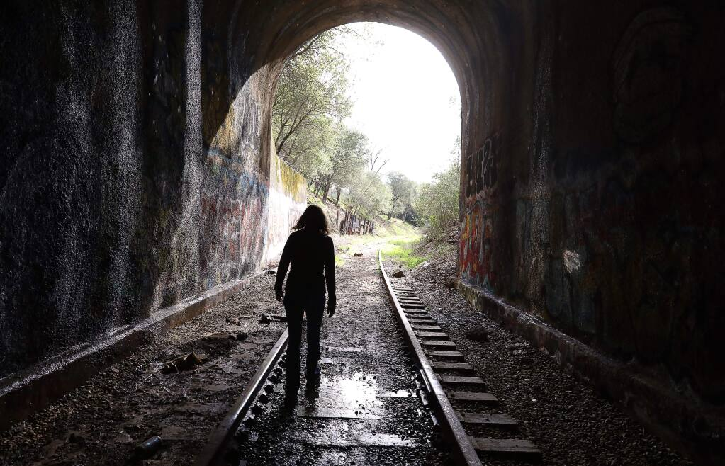 Caryl Hart, a North Coast Railroad Authority director, walks through a tunnel, in Cloverdale, where The Great Redwood Trail would travel along the rundown rail line from Larkspur to past Eureka, on Thursday, Feb. 7, 2019. (CHRISTOPHER CHUNG/ PD)