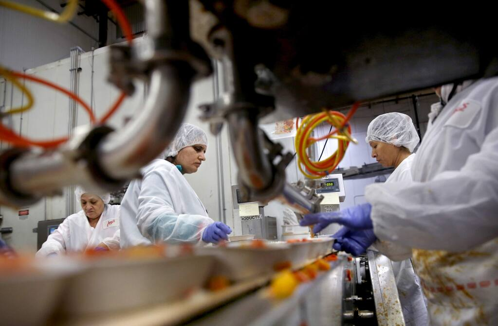 Amy's Kitchen employees Maria Angeles Lopez, Seema Radi, Felisa de los Santos de Ramirez, and Maria Guadalupe Cardenas put together Thai red curry frozen meals bound for Germany at the production plant on Wednesday, March 11, 2015. (BETH SCHLANKER/ The Press Democrat)