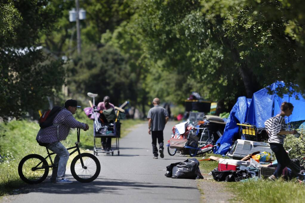 Members of the homeless community inhabit areas on either side of the Joe Rodota Trail next to the former Roseland homeless encampment in Santa Rosa on Thursday, April 19, 2018. (Beth Schlanker / The Press Democrat)