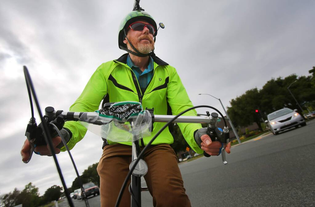 Sonoma Country Day School kindergarten teacher Steve Bush rides his bike home from work, along Airport Boulevard in Santa Rosa on Wednesday, May 10, 2017. Bush was named co-bike commuter of the year.(Christopher Chung/ The Press Democrat)