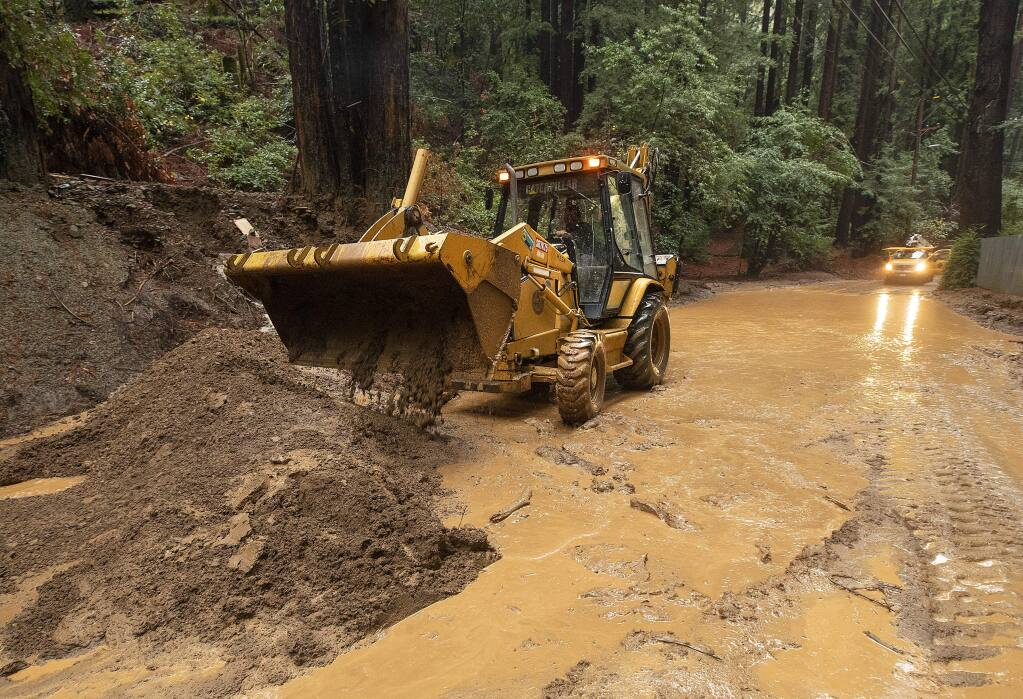 Road crews use a front end loader to clear mud and debris from the Bohemian Highway in Monte Rio on Monday, Dec. 2, 2019. (JOHN BURGESS/ PD)