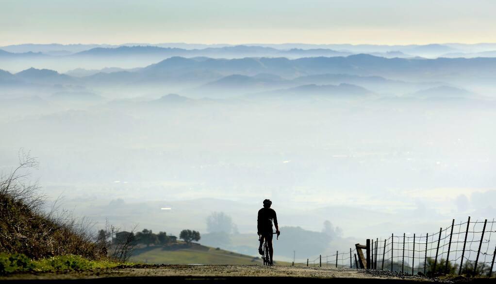 Chris Monson of Petaluma rides down Sonoma Mountain Road into a valley of smog on Tuesday, Jan. 6, 2015. (Kent Porter / The Press Democrat, 2015)