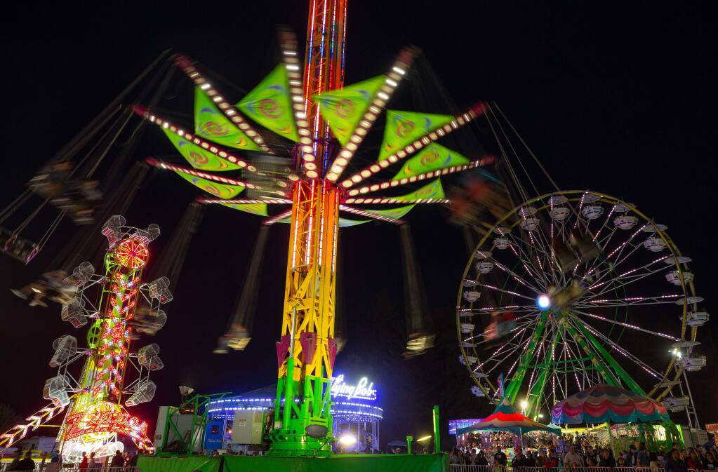 The swings of the Vertigo, center, slowly spin downward with the Zipper and Giant Wheel towering over the Midway crowds during the last weekend of the Sonoma County Fair, in Santa Rosa, California, on Friday, August 9, 2019. (Alvin Jornada / The Press Democrat)