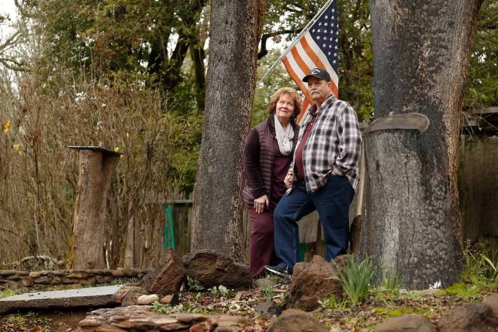 Sandi and Dave Cavanaugh stand for a portrait between two trees on their property that still bear burn marks from the Tubbs fire which destroyed their home of 26 years, off Mark West Springs Road, in Santa Rosa, California. Photographed on Friday, Jan. 11, 2019. (ALVIN JORNADA/ PD)