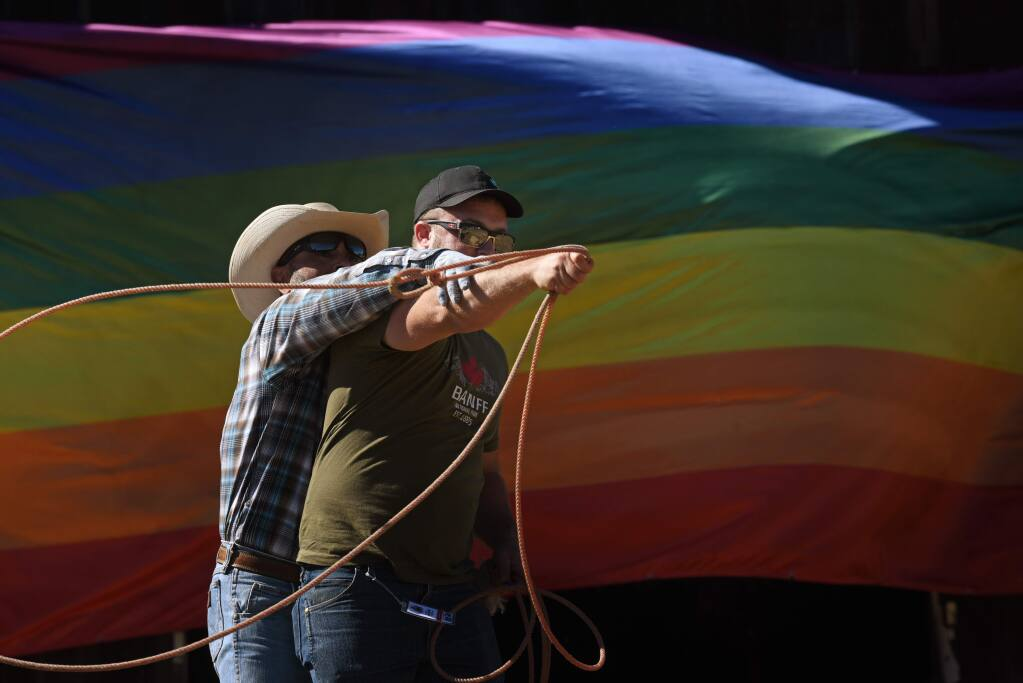 Bob Buenfil, of Los Angeles showing Jared Jiaconi, of San Francisco how to use a lasso during the Best Buck in the Bay LGBTQ rodeo held Sunday in Duncan Mills, California. September 15, 2019.(Photo: Erik Castro/for The Press Democrat)