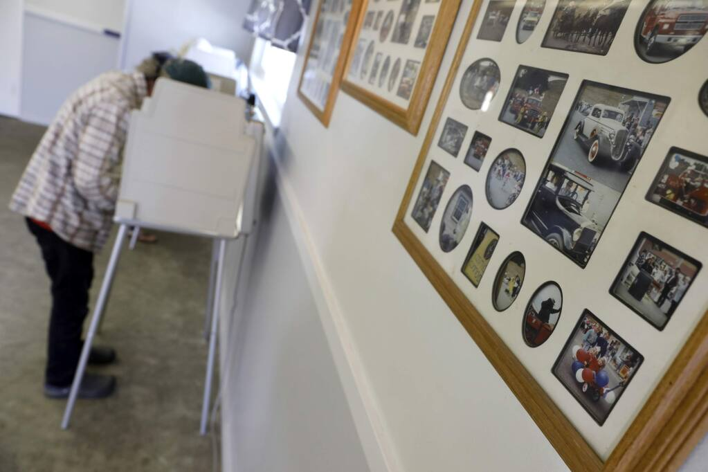 Photos of past community events hang on the wall in McCaughey Hall where Patrick Prather votes on Tuesday, June 5, 2018 in Bodega, California. (BETH SCHLANKER/ PD)