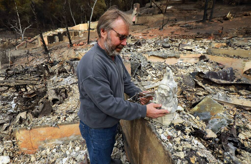 Hans Dippel sorts through the remains of his fire ravaged home on Chateau Ct. in Santa Rosa. One of the few unscathed items he found was a gnome given to him as a symbol of protection for the home when moved into the house off Parker Hill Rd. (photo by John Burgess/The Press Democrat)