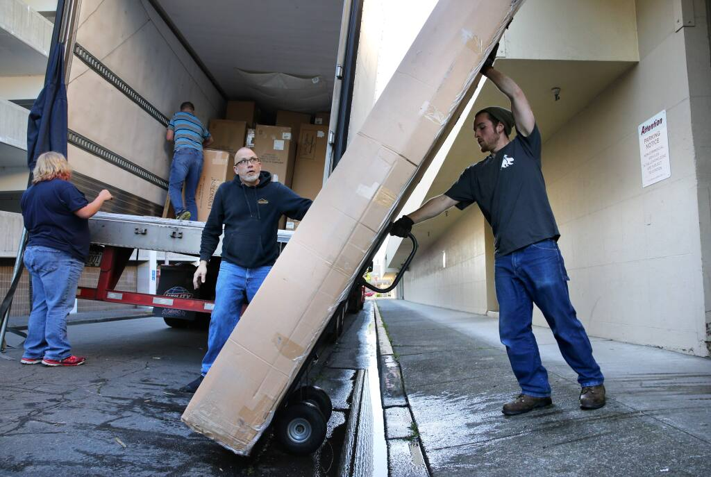 Assistant warehouse manager Aaron Navas, right, and his father, operations and service manager, Jim Navas, center, unload a shipment of furniture from North Carolina at the new Mark Thomas Home furniture store, formerly Pedersen's Furniture in Santa Rosa on Tuesday, April 9, 2019. (BETH SCHLANKER/ The Press Democrat)