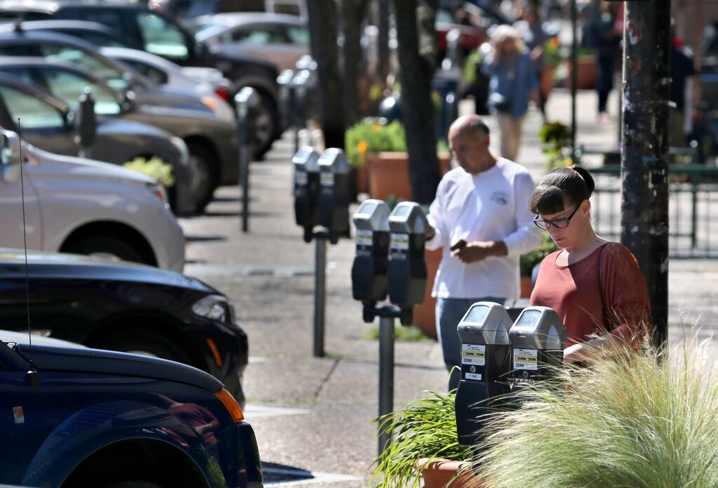 Rachel Markwardt, right, and and Tomas Cruz pay for parking at the meters on Fourth Street in Santa Rosa on Monday, March 18, 2019. (BETH SCHLANKER/ PD)