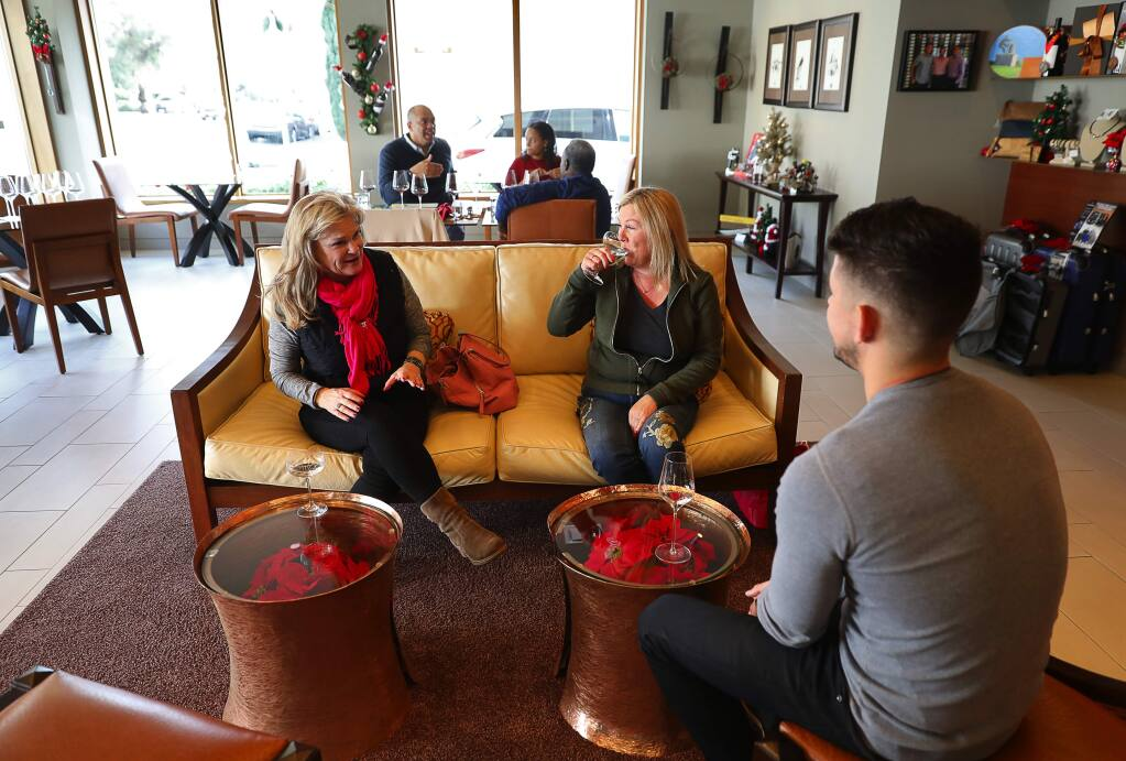 Tommi Hill, left, and Stephanie Van Cleave taste sparkling wine with general manager Brent Johnson at Corner 103 in Sonoma on Friday, December 15, 2017. (Christopher Chung/ The Press Democrat)