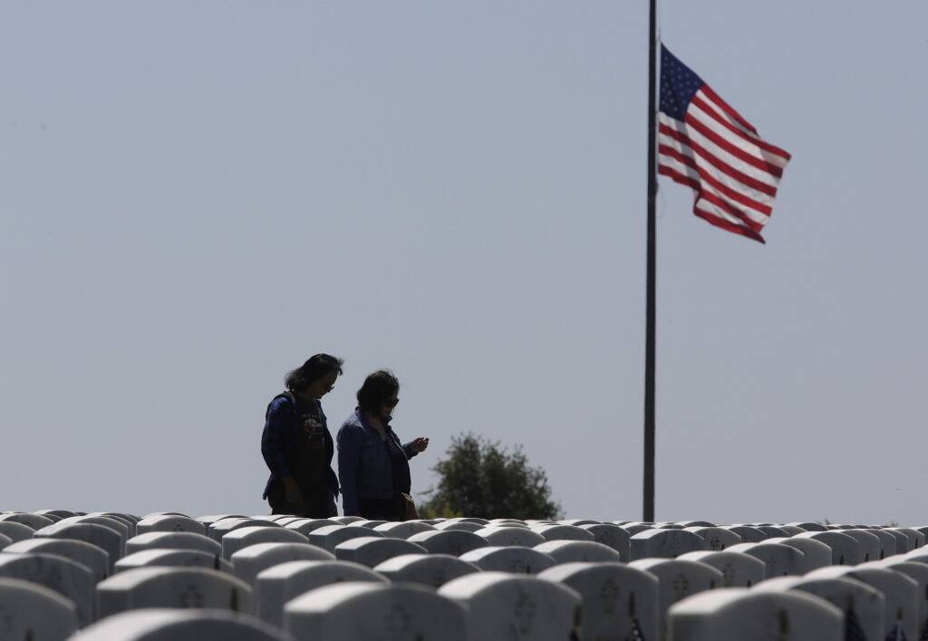 Visitors to the Sacramento Valley National Cemetery walk among the headstones, Monday, May 28, 2018, in Dixon, Calif. Californians across the state are paying their respects on Memorial Day to those who have died serving their country. (AP Photo/Rich Pedroncelli)