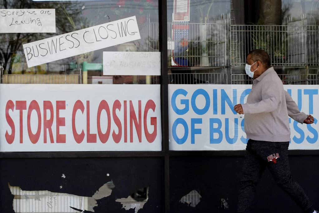 FILE - In this May 21, 2020 file photo, a man looks at signs of a closed store due to COVID-19 in Niles, Ill. In the North Bay, since November about a dozen employers filed notices of permanent and temporary job cuts. (AP Photo/Nam Y. Huh, File)
