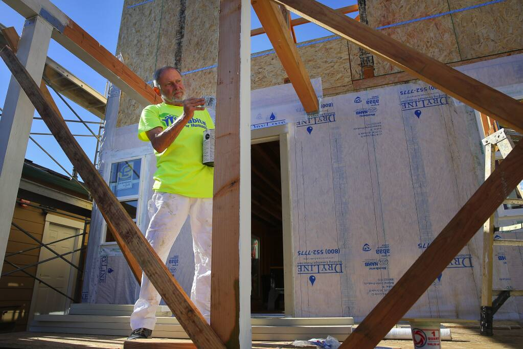 Habitat for Humanity volunteer Tom Dunbar paints a coat of primer on a home under construction in Cotati, on Thursday, November 12, 2015. (Christopher Chung/ The Press Democrat)