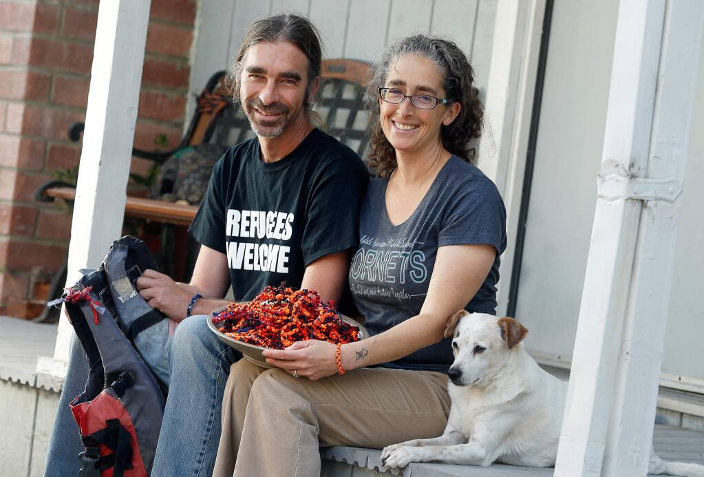 Mary Beth and Eric Leland pose for a portrait at their home in Petaluma, California, on Wednesday, August 29, 2018. Mary Beth Leland began the Refugee Hopelet Project which sells bracelets, dubbed hopelets, made of material from the discarded life jackets of refugees' journeys across the Mediterranean Sea. All the donations are given to refugee families and a Greek nonprofit. (Alvin Jornada / The Press Democrat)