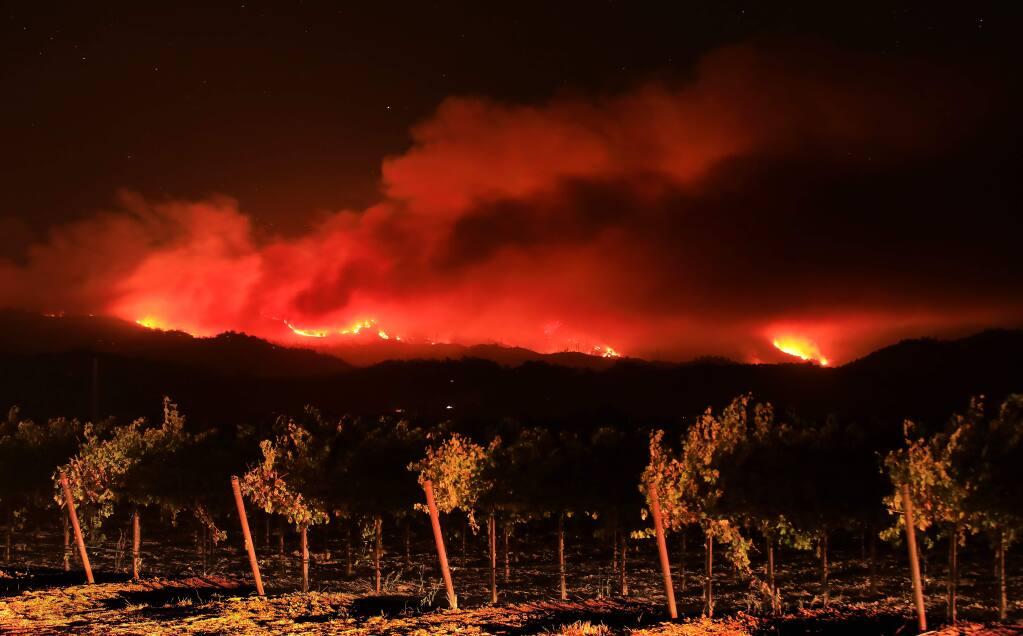 Headlights illuminate a vineyard in the Alexander Valley as the the Kincade fire burns in the Mayacamas Mountains on Oct. 25, 2019. (KENT PORTER / The Press Democrat)