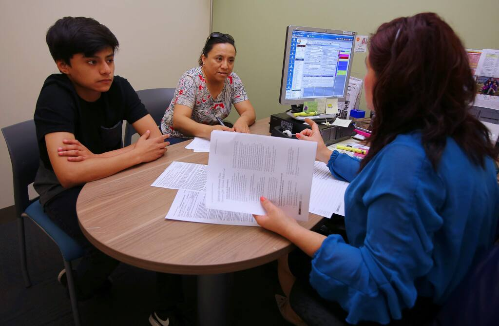 Outreach coordinator Elia Solar helps Araceli Uribe fill out paperwork for her undocumented son, Jafet Azpeitia, 15, to sign up for Medi-Cal, at the Petaluma Health Center, in Petaluma, on Thursday, May 12, 2016. (Christopher Chung / The Press Democrat)