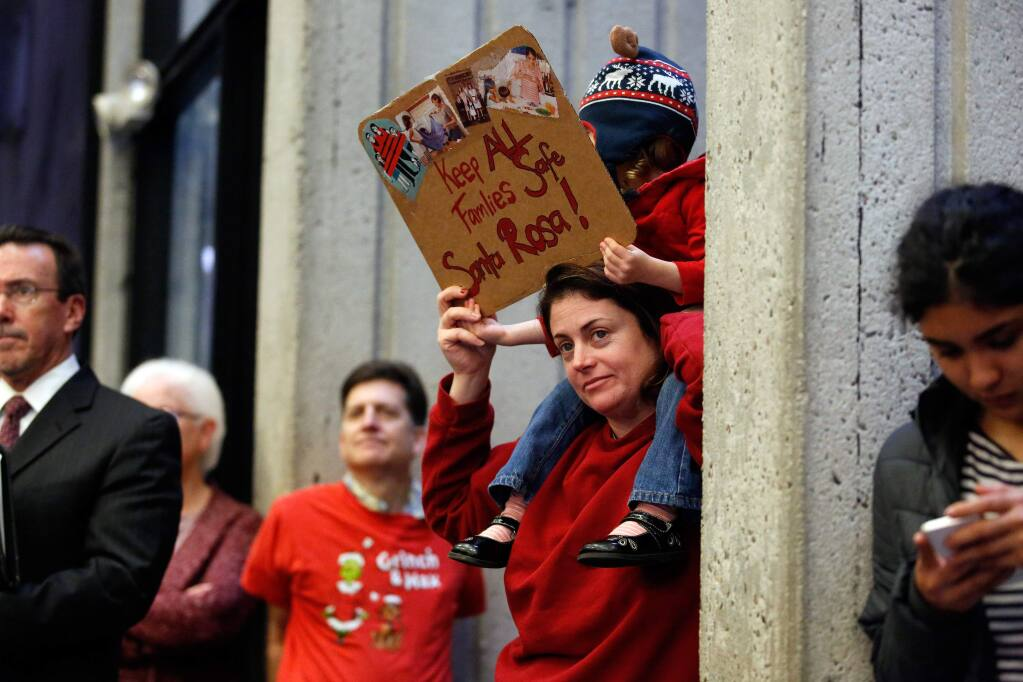 Cara Baum and her daughter Sirsha, 2, hold a sign in support of giving safe haven to undocumented immigrants during a city council meeting discussing the sanctuary city proposal in Santa Rosa, California on Tuesday, Feb. 7, 2017. (Alvin Jornada / The Press Democrat)