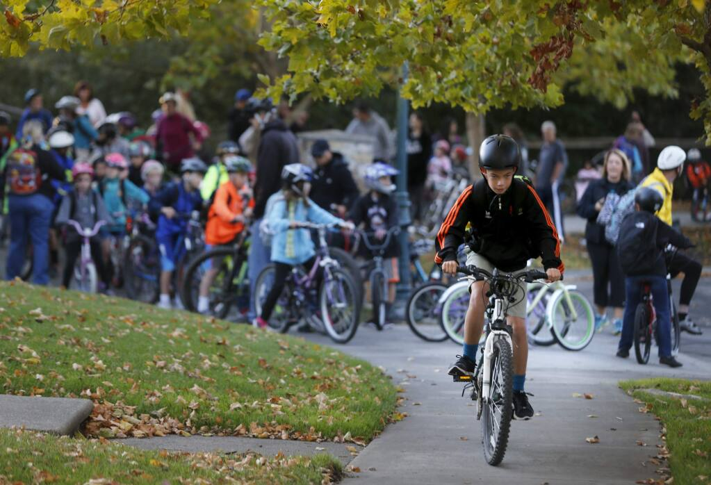 Dominic Dadalt, 12, rides in front of a bike train of Sonoma Mountain Elementary School students for Walk and Roll to School Day on Wednesday, October 5, 2016 in Petaluma, California . (BETH SCHLANKER/ The Press Democrat)