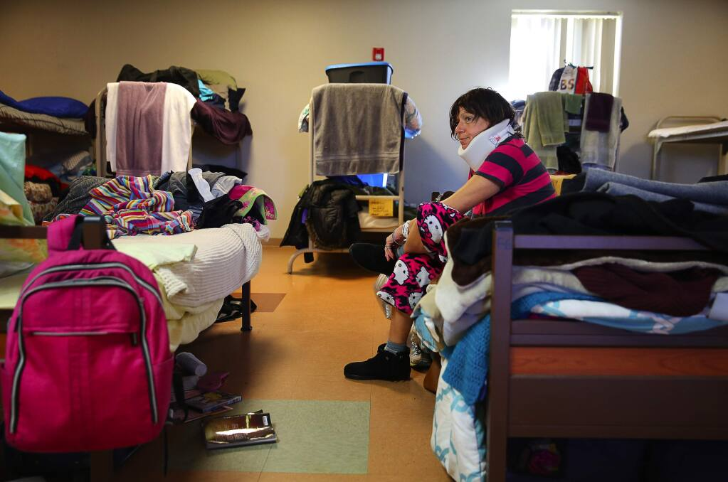 Carol Swann slips on her shoes in the large dorm room at Catholic Charities' Samuel L. Jones Hall homeless shelter in Santa Rosa on Tuesday, February 28, 2017. Swann has been staying at the shelter since early January.(Christopher Chung/ The Press Democrat)