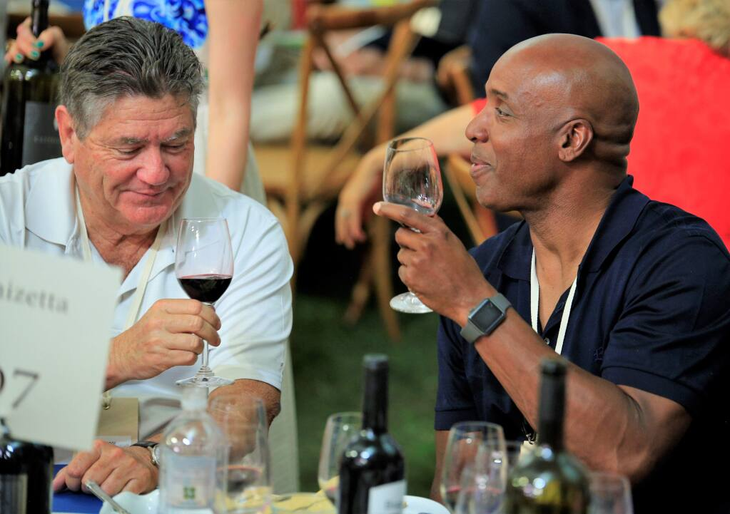 Barry Bonds (right) and Fred Biagi toast as the Auction heats up at the Auction Napa Valley, Saturday June 2nd, 2018 at Meadowood Napa Valley in Saint Helena California. (Photo Will Bucquoy / For the Press Democrat).