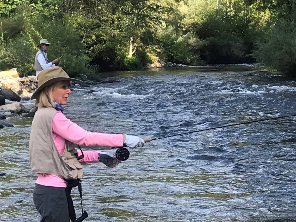 JEANNE MONTAGUE casts a fly toward a waiting rainbow trout on the upper Sacramento River while her husband, Chad Overway, fishes just upstream. (Submitted)