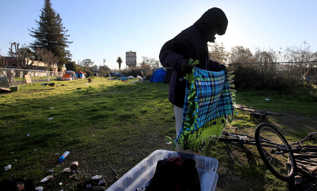 Edmund Wilson thoughtfully clears his encampment along the Joe Rodota Trail after Sonoma County Regional Parks officials gave a group experiencing homelessness an 8 a.m. deadline to move off the trail on Wednesday, Feb. 24, 2021, in Santa Rosa. (Kent Porter / The Press Democrat)