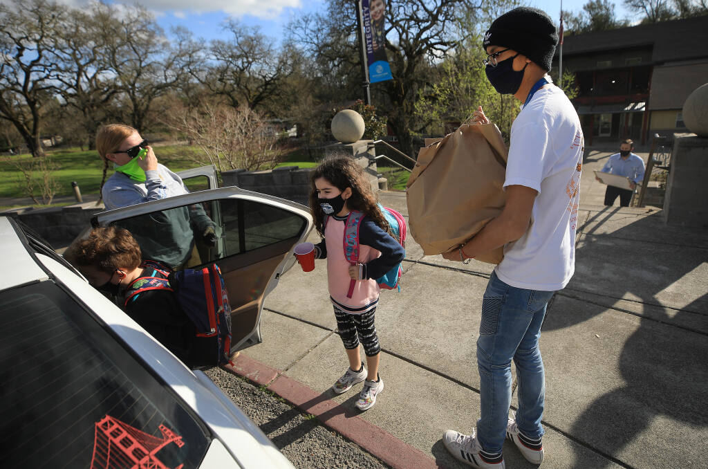 Boys and Girls Club staffer Pradbe Watthnnawes carries prepared food to Katie Estupian and her children, Enzo, 8, left, and Fiona, 6, Friday, March 5, 2021, in Sonoma. The food was prepared by Elaine Bell Catering, after a wedding was canceled and the couple to be married donated $20,000 worth of food to go to various organizations that help people in need. (Kent Porter / The Press Democrat) 2021