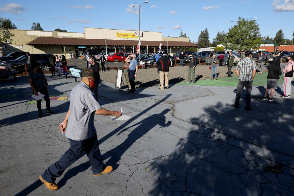 People wait in line for free COVID-19 testing outside the Roseland Community Library in Santa Rosa, California on Thursday, November 19, 2020. (Beth Schlanker/ The Press Democrat)