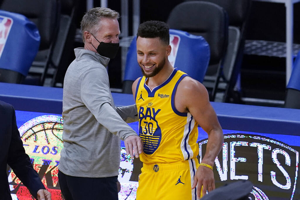Golden State Warriors head coach Steve Kerr, left, celebrates with guard Stephen Curry after the Warriors defeated the Milwaukee Bucks in San Francisco on Tuesday, April 6, 2021. (Jeff Chiu / ASSOCIATED PRESS)