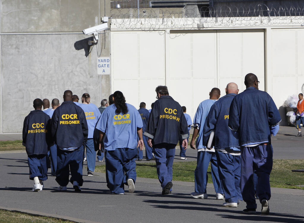 FILE - In this Feb. 26, 2013, file photo, inmates walk through the exercise yard at California State Prison Sacramento, near Folsom, Calif. California is giving 76,000 inmates, including violent and repeat felons, the opportunity to leave prison earlier as the state aims to further trim the population of what once was the nation's largest state correctional system. The new rules take effect Saturday, May 1, 2021, but it will be months or years before any inmates go free earlier.   (AP Photo/Rich Pedroncelli, File)