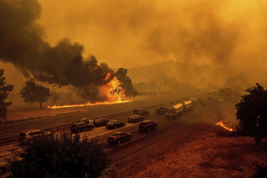 Flames from the LNU Lightning Complex fires jump Interstate 80 in Vacaville on Aug. 19. (NOAH BERGER / Associated Press)