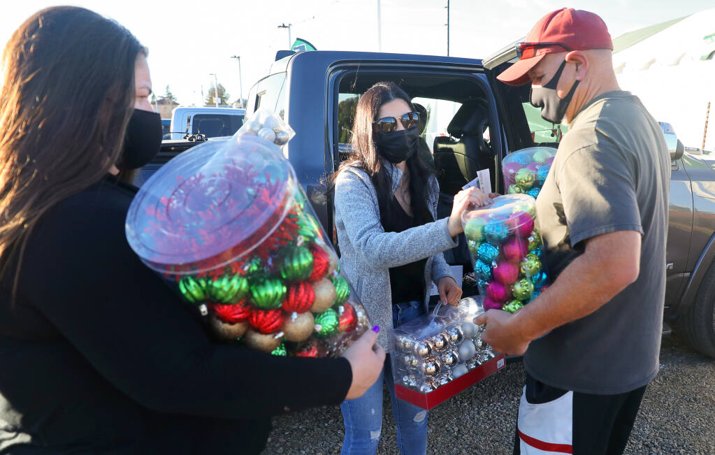 Tory Crowder, center, and her father, Dave Puentes, provide Christmas trees and ornaments to Sara Gonzales for women with children housed by Women's Recovery Services, at Mark's Christmas Tree Lot in Santa Rosa on Monday, Dec. 7, 2020. (Christopher Chung / The Press Democrat)