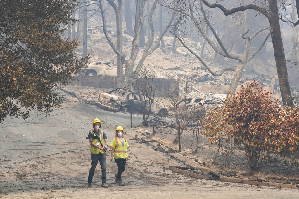 Workers with Davey Resource Group asess the damage to the trees in a neighborhood Tuesday, Aug. 25, 2020, in Boulder Creek, Calif.,after the the CZU August Lightning Complex Fire passed by. (AP Photo/Marcio Jose Sanchez)