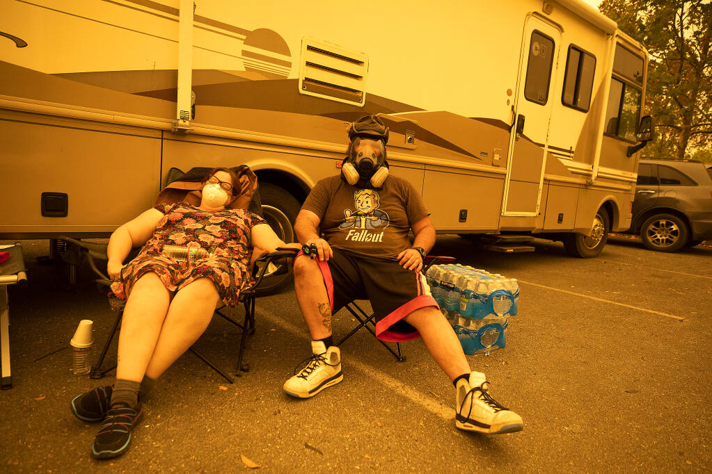 Crickett, left, and Josh Green try and get some sleep on Monday morning, Sept. 28, 2020, in the parking lot of A Place to Play in Santa Rosa. The pair evacuated their Los Alamos Road home with their extended family last night as the Glass fire approached.  (John Burgess/The Press Democrat)