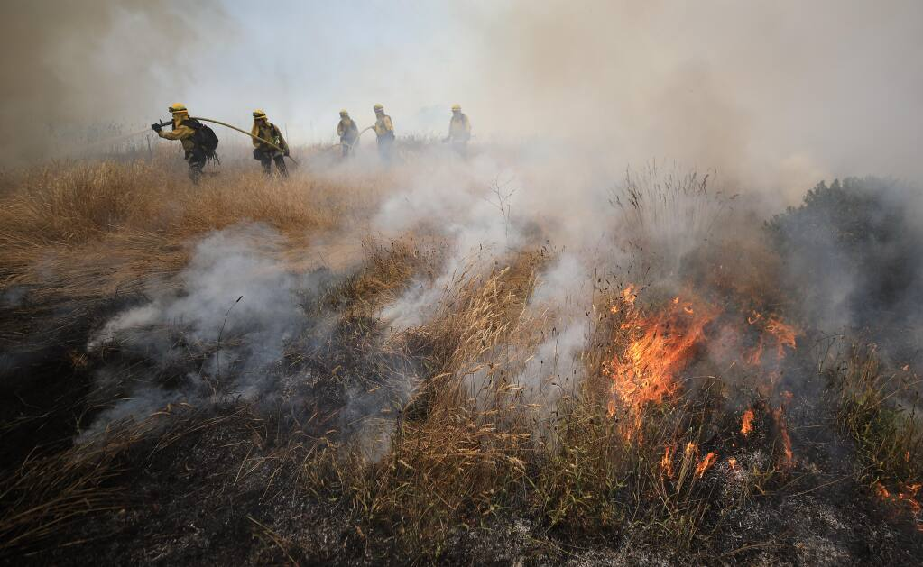 Cal Fire firefighters douse flames from a spot fire during a prescribed burn south of Fort Ross, Wednesday, July 1, 2020.  (Kent Porter / The Press Democrat)