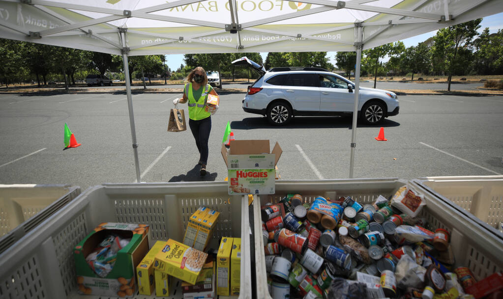 Cassidy Jourdan of the Redwood Empire Food Bank takes in donated grocery items, Wednesday, July 22, 2020 at a Place to Play in Santa Rosa. (Kent Porter / The Press Democrat) 2020