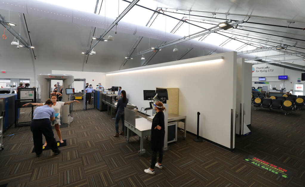 Travelers proceed through the newly relocated TSA security checkpoint, which occupies the expanded area of the passenger departure tent, at the Charles M. Schulz-Sonoma County Airport near Santa Rosa, on Thursday, Oct. 29, 2020. (Christopher Chung / The Press Democrat)