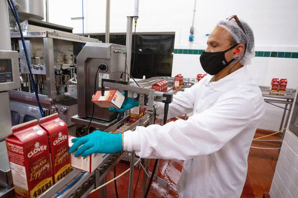 Bottling line worker Felix Sanchez conducts a quality control test on the packaging of Clover Sonoma premium organic eggnog, in Petaluma, California, on Thursday, December 10, 2020. (Alvin A.H. Jornada / The Press Democrat)
