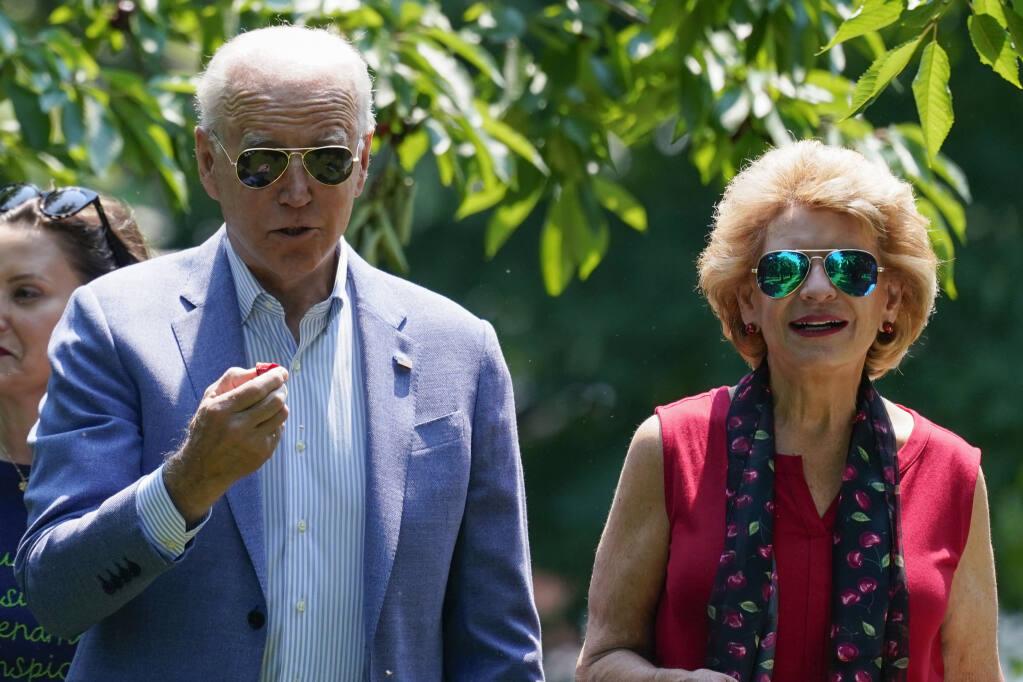 President Joe Biden eats a cherry as he tours King Orchards fruit farm Sen. Debbie Stabenow, D-Mich., Saturday, July 3, 2021, in Central Lake, Mich. (AP Photo/Alex Brandon)