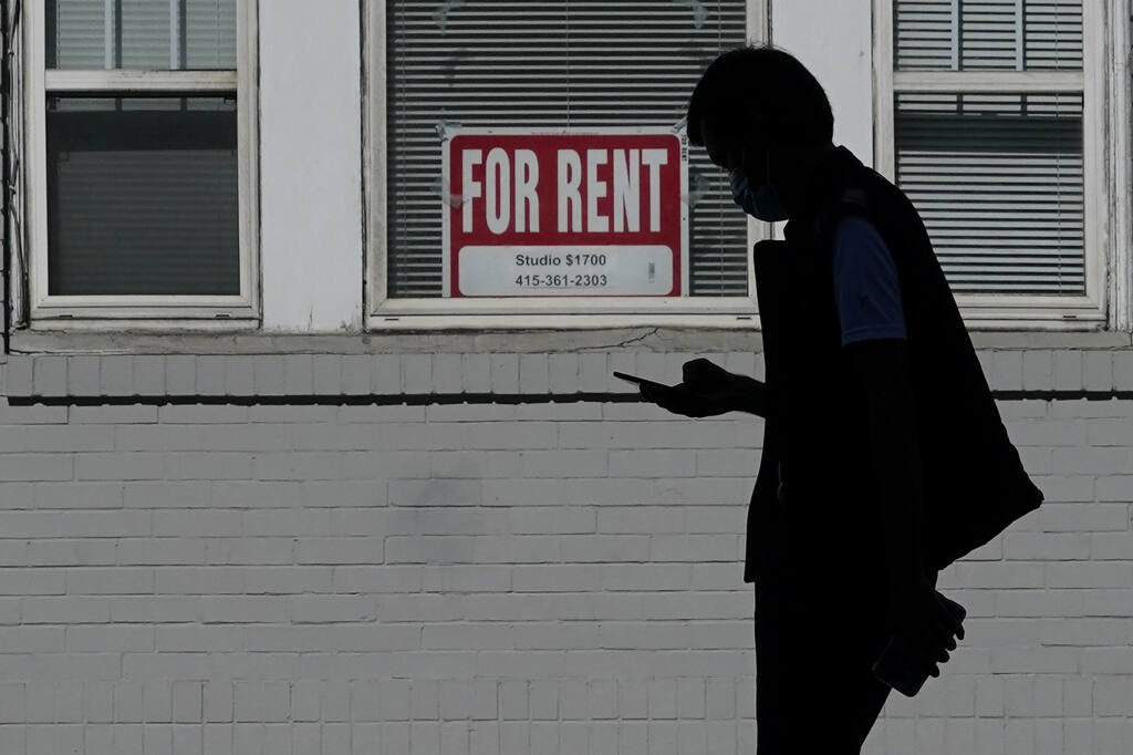 A man walks in front of a For Rent sign in a window of a residential property in San Francisco, Tuesday, Oct. 20, 2020. (AP Photo/Jeff Chiu)
